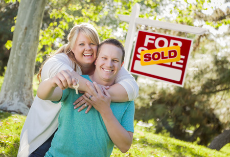 Happy Couple Holding House Keys In Front of Sold Real Estate Sign