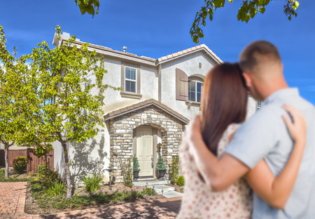 Affectionate Military Couple Looking at Nice New House  photo