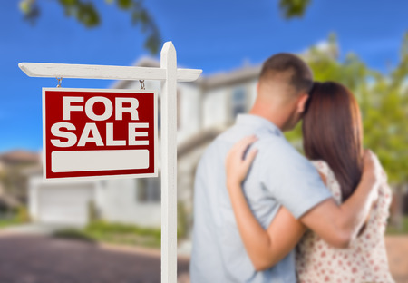 For Sale Real Estate Sign and Affectionate Military Couple Looking at Nice New House  photo