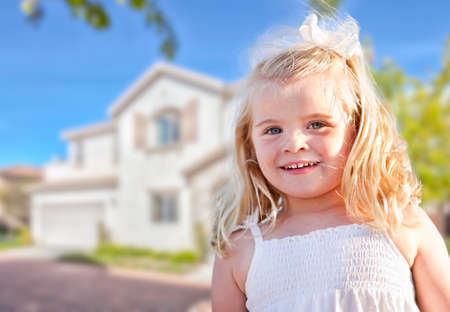 Cute Smiling Girl Playing in Front Yard of House  photo