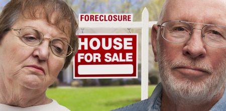 repossessed: Depressed Senior Couple in Front of Foreclosure Real Estate Sign and House.
