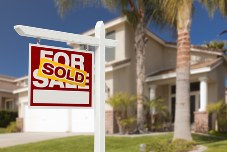 purchase: Sold Home For Sale Real Estate Sign in Front of Beautiful New House. Stock Photo