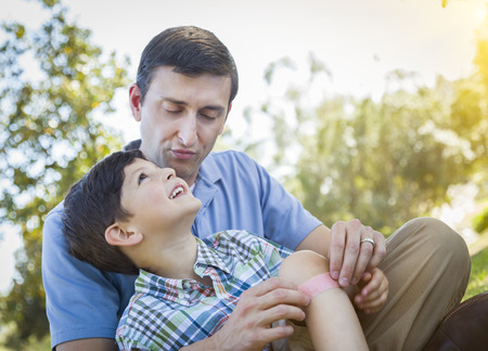 Loving Father Puts a Bandage on the Knee of His Young Son in the Park. photo