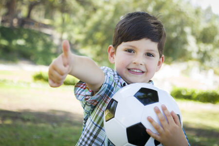 kids exercise: Cute Young Boy Playing with Soccer Ball Outdoors in the Park. Stock Photo
