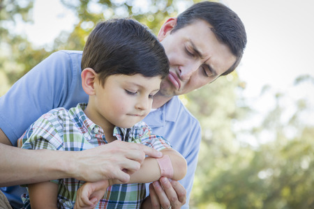 Loving Father Puts a Bandage on the Elbow of His Young Son in the Park. photo