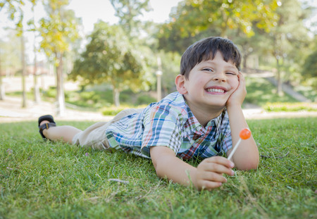 Handsome Young Boy Enjoying His Lollipop Outdoors on the Grass. photo