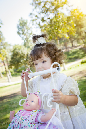 1 year old: Adorable Young Baby Girl Playing with Her Baby Doll and Carriage Outdoors.