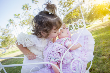 mixed race girl: Adorable Young Baby Girl Playing with Her Baby Doll and Carriage Outdoors.