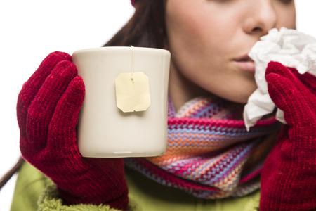tejido: Mujer enferma joven con el tejido que sostiene la taza con la bolsita de té blanco que cuelga.