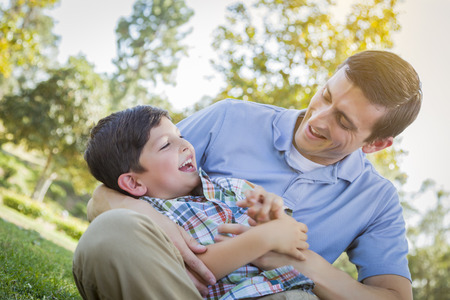 horsing around: Loving Young Father Tickling Son in the Park.