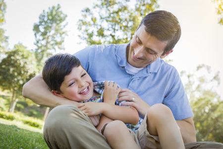 family tickle: Loving Young Father Tickling Son in the Park.