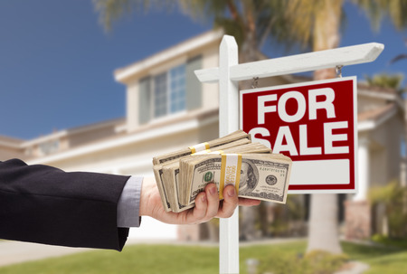 house sale: Buyer Handing Over Cash for House with Home and For Sale Real Estate Sign Behind. Stock Photo