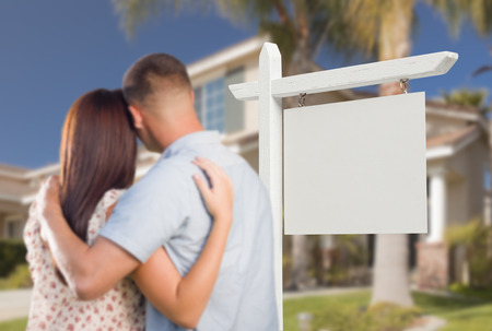 Blank Real Estate Sign and Military Couple Looking at Nice New House. photo