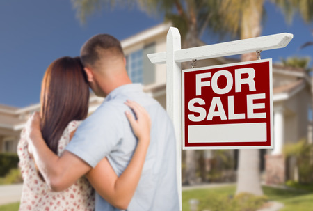 For Sale Real Estate Sign and Military Couple Looking at Nice New House. photo