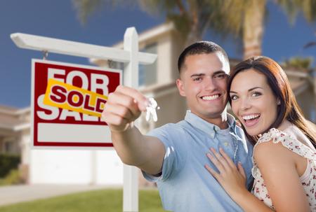 pareja en casa: Mixed Race Emocionado Pareja militar en frente de la casa nueva con nuevas claves de la casa y vende Inmobiliaria cartel fuera. Foto de archivo