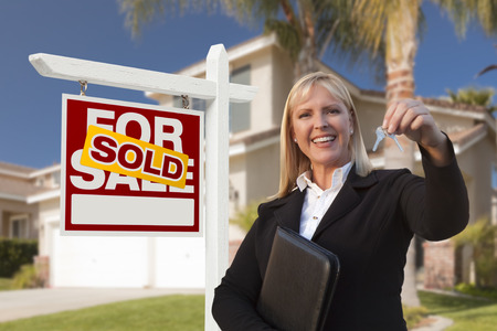 Female Real Estate Agent Handing Over the House Keys in Front of a Beautiful New Home and Real Estate Sign.