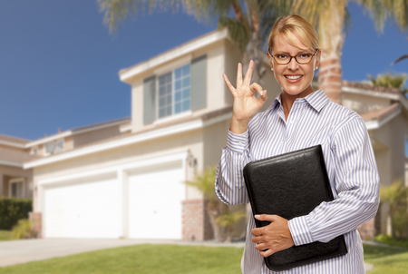 vacant: Attractive Businesswoman with Okay Hand Sign In Front of Nice Residential Home. Stock Photo