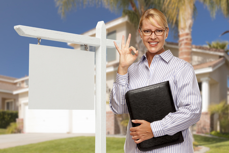 Attractive Female Real Estate Agent in Front of Blank Real Estate Sign and House. Stock Photo - 28264577