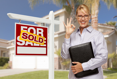 Attractive Female Real Estate Agent in Front of Sold Home For Sale Sign and House. Stock Photo - 28264578