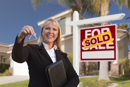 house sale: Female Real Estate Agent Handing Over the House Keys in Front of a Beautiful New Home and Real Estate Sign.