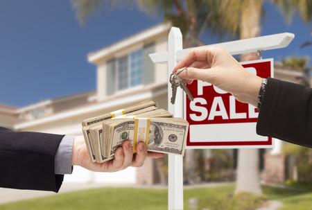 エージェントは、買い手が家との販売の不動産記号の後ろに家のための現金上渡すキーを引き渡します。 写真素材