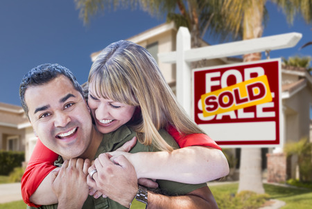Happy Hugging Mixed Race Couple in Front of Sold Home For Sale Real Estate Sign and House. photo