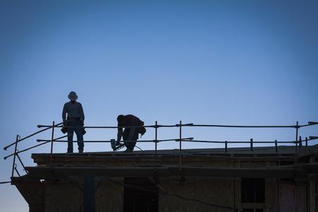 建物の屋根の上の建設労働者のシルエット