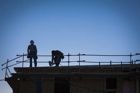 Construction Workers Silhouette on Roof of Building