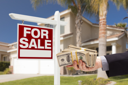 Buyer Handing Over Cash for House with Home and For Sale Real Estate Sign Behind  photo