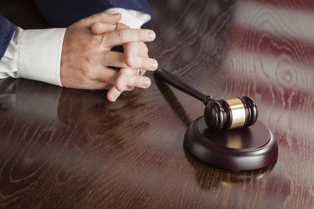 orden judicial: Juez Masculino Descansa manos cruzadas detrás de Mazo con la reflexión de la bandera americana en la tabla de madera