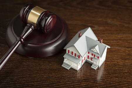 ruling: Gavel and Small Model House on Wooden Table. Stock Photo