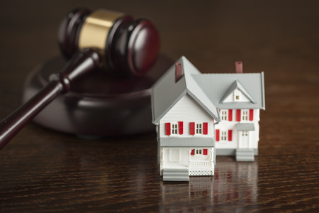 Gavel and Small Model House on Wooden Table. photo