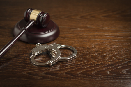 cuffs: Gavel and Pair of Handcuffs on Wooden Table. Stock Photo