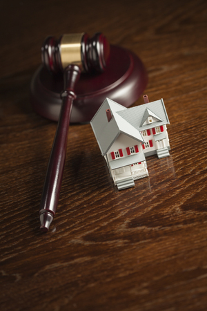 bank owned: Gavel and Small Model House on Wooden Table. Stock Photo