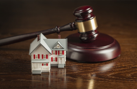 owned: Gavel and Small Model House on Wooden Table. Stock Photo