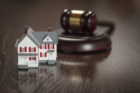 foreclosure: Gavel and Small Model House on Wooden Table. Stock Photo