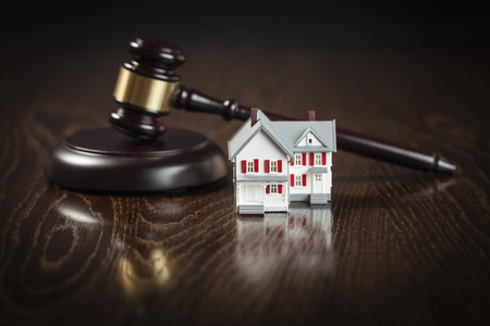 Gavel and Small Model House on Wooden Table. Stock Photo