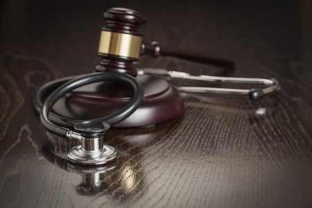 Gavel and Stethoscope on Reflective Wooden Table. photo