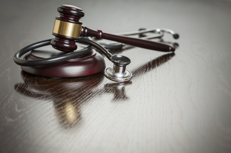 ethics: Gavel and Stethoscope on Reflective Wooden Table.