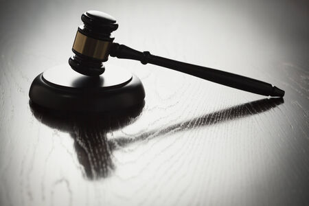 Dramatic Gavel Silhouette on Reflective Wood Surface. Banque d'images