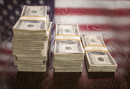 american dollar: Thousands of Dollars Stacked with Reflection of American Flag on Wooden Table.