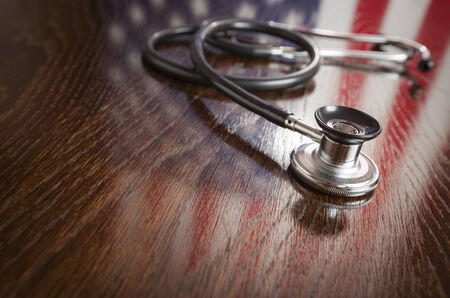 american health care: Stethoscope with American Flag Reflection on Wooden Table.
