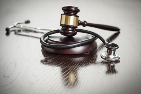 derecho penal: Mazo y estetoscopio en mesa de madera reflectante. Foto de archivo