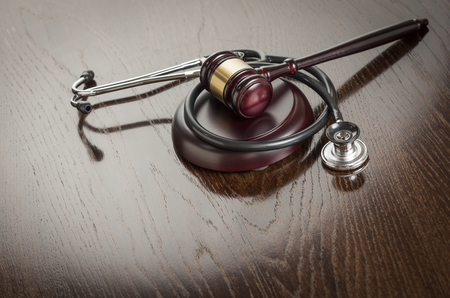 health industry: Gavel and Stethoscope on Reflective Wooden Table.