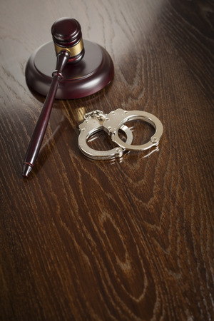 Gavel and Pair of Handcuffs on Wooden Table. photo