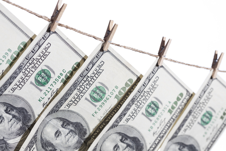cleaning debt: Hundred Dollar Bills Hanging From Clothesline on a White Background.