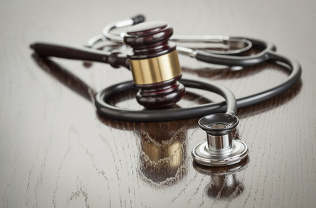 negligence: Gavel and Stethoscope on Reflective Wooden Table.
