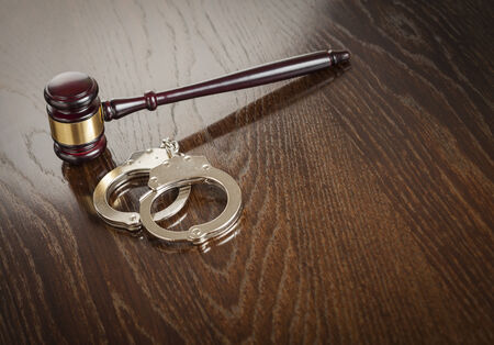 shackle: Gavel and Pair of Handcuffs on Wooden Table. Stock Photo