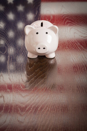 american dream: Piggy Bank with an American Flag Reflection on Wooden Table.