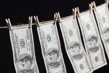 Hundred Dollar Bills Hanging From a Clothesline on a Dark Background.